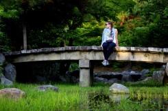 Zátišie v príjemnom parku a modelka hompáľajúca nohy ponad potôčikom